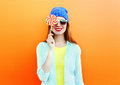 Portrait of happy pretty smiling woman and lollipop over colorful orange Royalty Free Stock Photo