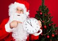 Portrait of a happy santa holding clock over red background Stock Images