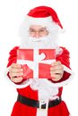 Portrait of a happy santa holding gift over white background Royalty Free Stock Photos