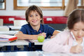 Portrait of happy schoolboy drawing at classroom with female classmate in foreground Royalty Free Stock Photos