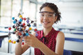 Portrait of happy schoolgirl experimenting molecule model in laboratory