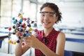 Portrait of happy schoolgirl experimenting molecule model in laboratory