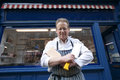 Portrait of a happy senior butcher standing with crossed cleavers in hands outside shop Stock Photography