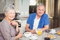 Portrait of happy senior couple having breakfast at table Royalty Free Stock Image