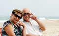 Portrait of happy senior couple sitting together on a beach Royalty Free Stock Images
