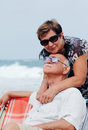 Portrait of happy senior couple sitting together on a beach Stock Photography