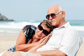 Portrait of happy senior couple sitting together on a beach Stock Images