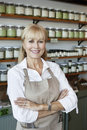 Portrait of a happy senior employee with arms crossed in spice store Royalty Free Stock Photo