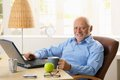 Portrait of happy senior man with computer sitting at desk using laptop at home smiling at camera Stock Images