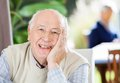 Portrait of happy senior man at nursing home sitting with grandson in background Royalty Free Stock Photos