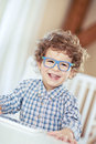 Portrait of happy smiling beautiful little boy with glasses in babyroom - checked shirt Royalty Free Stock Photo