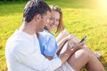 Portrait of happy smiling caucasian couple sitting together on t the grass outdoors and listening to music horizontal image Stock Image