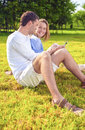 Portrait of happy smiling caucasian couple sitting together on t the grass outdoors and listening to music vertical image Stock Photography