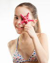 Portrait of happy smiling girl holding starfish at eye Royalty Free Stock Photo
