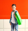 Portrait happy smiling little boy teenager with shopping bag in city