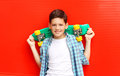 Portrait happy smiling teenager boy wearing a checkered shirtwith skateboard in city
