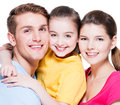 Portrait of happy smiling young family with kid in colored shirts looking at camera isolated on white Royalty Free Stock Images