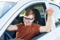 Portrait of happy smiling young man, buyer sitting in his new car and showing keys outside dealer office. Personal Royalty Free Stock Photo