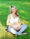 Portrait happy smiling young pregnant woman sitting on grass doing yoga