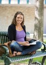 Portrait of happy student studying on bench female at university campus Stock Photography