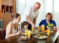 Portrait of happy three generations family posing together over healthy table at home interior Stock Photos