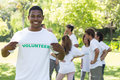 Portrait of happy volunteer holding tshirt with friends disucssing in background Stock Images