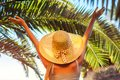 Portrait of happy woman in hat lifting hands under palm leaf in hotel yard. Summer vacation