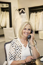 Portrait of a happy woman listening to telephone receiver in bridal store Royalty Free Stock Image