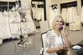 Portrait of a happy woman making a call in bridal store Royalty Free Stock Photography