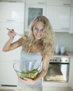 Portrait of happy woman mixing salad in kitchen Stock Image