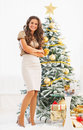 Portrait of happy woman standing in front of christmas tree full length young Royalty Free Stock Image