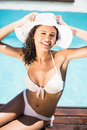 Portrait of happy woman wearing white hat and bikini relaxing by pool side Royalty Free Stock Photo
