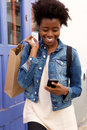 Happy young african american woman walking with cellphone and shopping bags Royalty Free Stock Photo