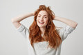 Portrait of happy young beautiful redhead girl smiling looking at camera touching hair over white background. Royalty Free Stock Photo
