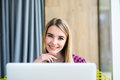 Portrait of happy young beauty woman using laptop at office table or cafe. Royalty Free Stock Photo