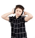 Portrait of a happy young boy listening to music on headphones against white background Royalty Free Stock Images