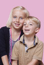 Portrait of happy young boy with sister over pink background Stock Photo