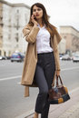 Portrait of happy young brunette woman in beige coat talking on Royalty Free Stock Photo