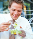 Portrait of happy young businessman eating salad Royalty Free Stock Images