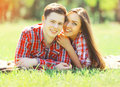 Portrait happy young couple having fun smiling lying on grass the in summer sunny day Stock Images