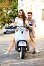 Portrait of happy young couple on scooter enjoying road trip in love riding a motorbike handsome guy and sexy women travel riders Stock Images