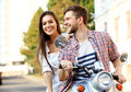 Portrait of happy young couple on scooter enjoying road trip in love riding a motorbike handsome guy and sexy women travel riders Royalty Free Stock Image