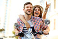 Portrait of happy young couple on scooter enjoying road trip in love riding a motorbike handsome guy and sexy women travel riders Royalty Free Stock Photos