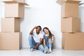 Portrait of happy young couple sitting on floor looking at camera and dreaming their new home and furnishing.