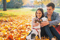 Portrait of happy young couple sitting outdoors in autumn park Royalty Free Stock Photo