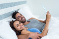 Portrait of happy young couple with tablet while lying on bed Royalty Free Stock Photo