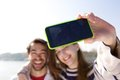 Portrait of a happy young couple taking selfie with mobile phone close up self Stock Photo