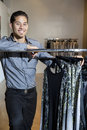 Portrait of a happy young male standing by clothes rack in fashion store Royalty Free Stock Photo
