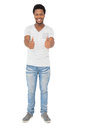 Portrait of a happy young man gesturing thumbs up full length over white background Royalty Free Stock Image