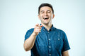 Portrait happy young man, laughing, pointing with finger at some Royalty Free Stock Photo